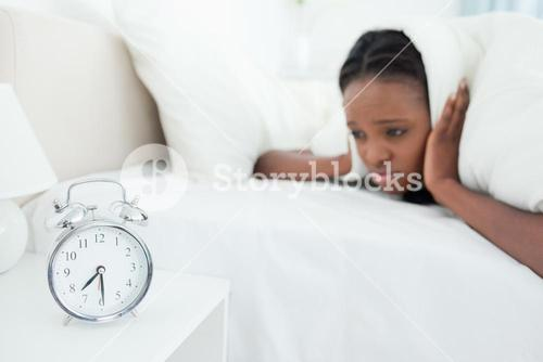 Woman being awakened by her alarm clock