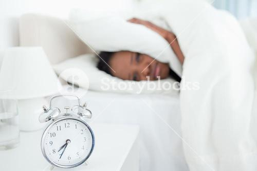 Exhausted woman covering her ears while her alarm clock is ringing