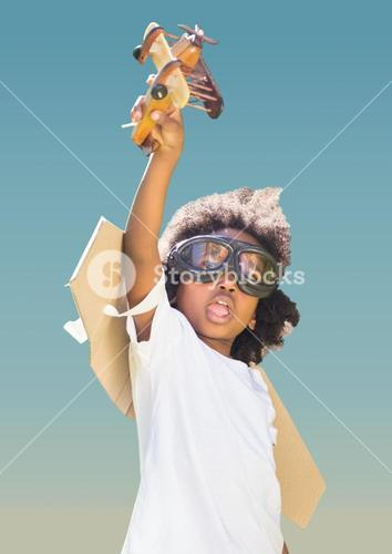 Superhero kid in flying goggles playing with toy aeroplane