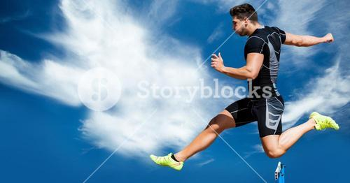 Male athlete jumping over the hurdles