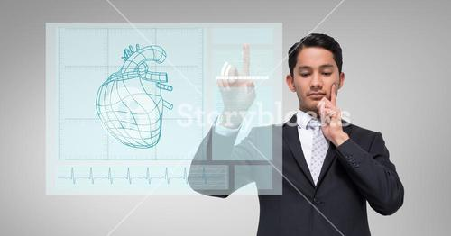 Thoughtful businessman touching human heart graphic on a digital wall