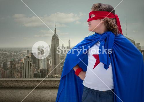 Superhero kid in blue cape and red eye mask standing with cityscape in background