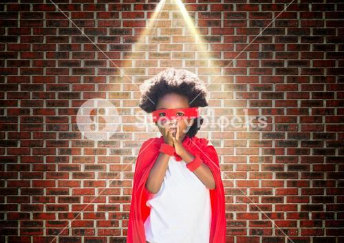 Superhero kid in red cape and eye mask standing against brick wall