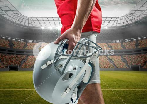 Mid section of an American football player holding helmet in stadium