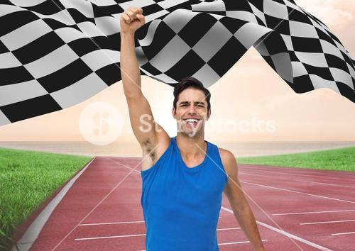 Male athlete raising hands at finishing point with checker flag