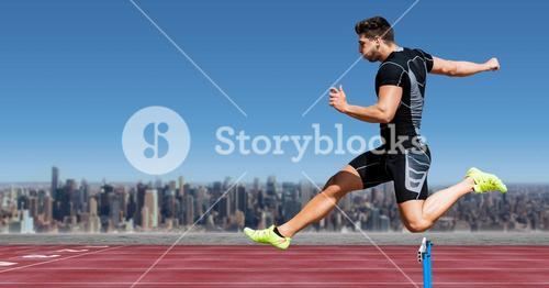 Athlete jumping over a hurdle on race track against cityscape in background