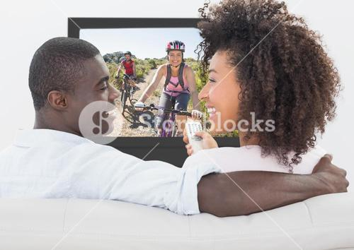 Couple talking while watching television at home