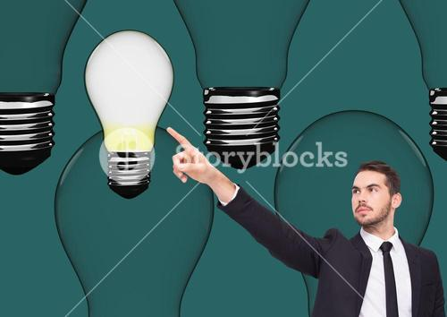 Businessman pointing at light bulb against green background