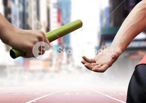 Athletes passing the baton during relay race against city buildings