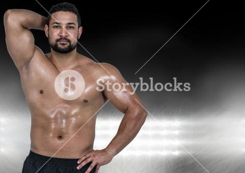 Muscular man posing against black illuminated background
