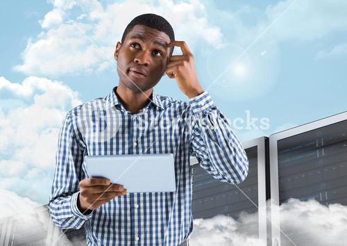 Thoughtful man holding digital tablet against server systems in sky
