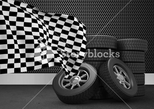 Stack of tires with checkered flag against black background
