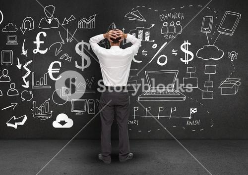 Confused businessman standing against business symbols in background