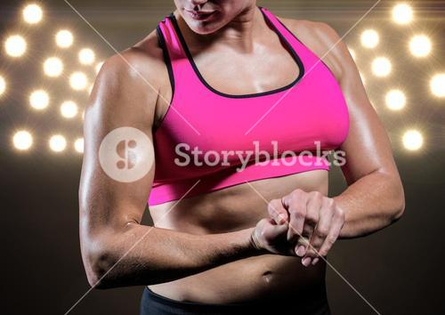 Strong woman posing against black illuminated background