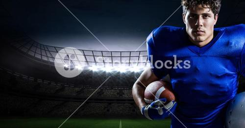 American football player holding rugby ball against stadium in background