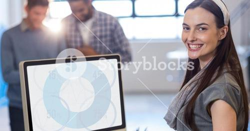 Woman smiling while using desktop pc at office