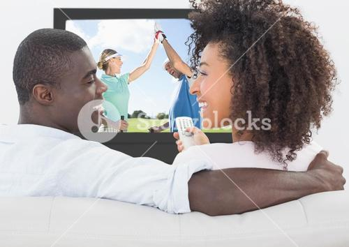 Couple smiling while watching golf on television