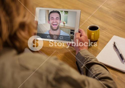 Woman having a video call with her friend on digital tablet