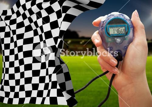 Stopwatch and checkered flag against stadium in background