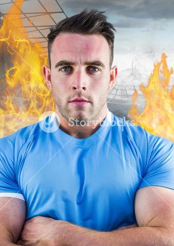 Athlete standing with his arms crossed against fire in background
