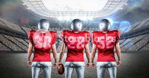 American football players standing against stadium in background