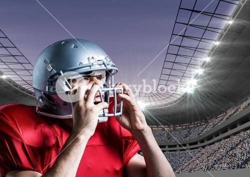 American football player removing his helmet against stadium in background