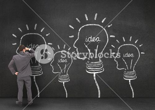Concept of thoughtful businessman looking at faced shape bulbs on wall