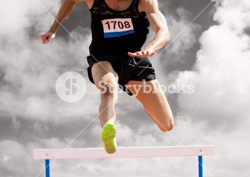 Athlete running over hurdle