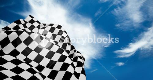 Checkered flag waving against cloudy sky