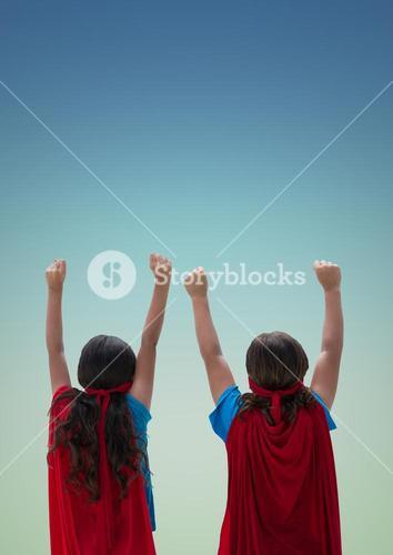Kids in red cape and mask standing with fist against turquoise background