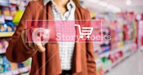 Mid-section of woman touching shopping cart on digital screen