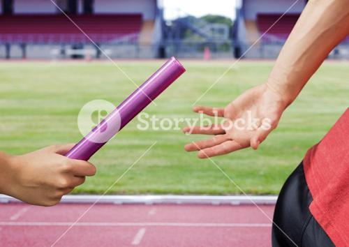 Mid-section of athlete passing the baton to teammate