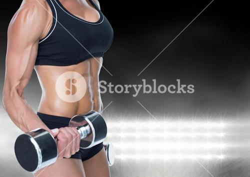 Mid-section of muscular woman lifting dumbell against bright light