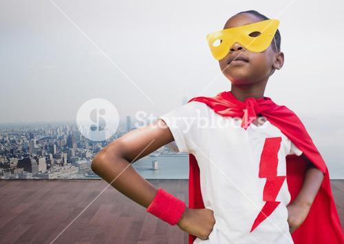 Kid wearing red cape and yellow mask standing with hand on hip against cityscape background