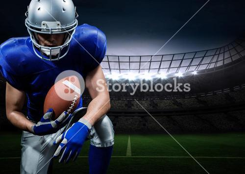 American football player posing with rugby ball in stadium