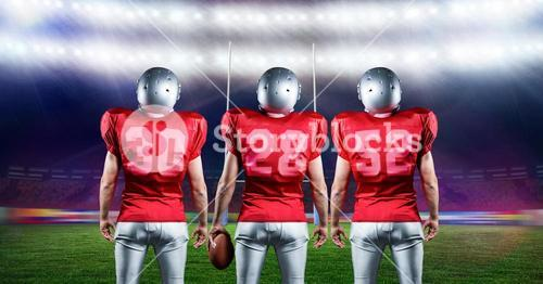 American football players standing with rugby ball in stadium
