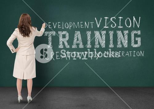 Rear view of businesswoman writing business terms on chalkboard