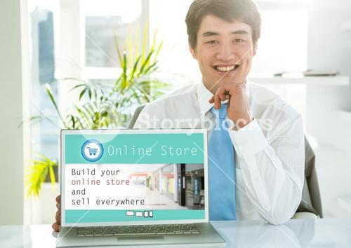 Portrait of smiling man showing online store on laptop screen