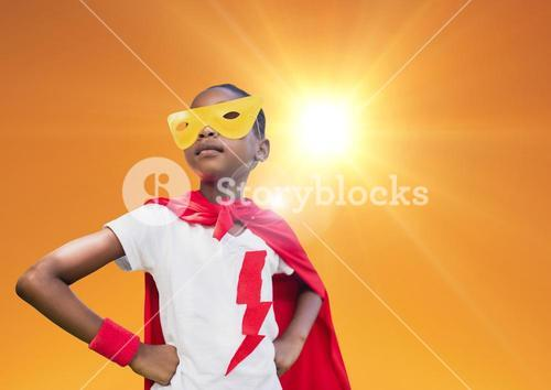 Super kid in red cape and yellow mask standing with hand on hip against bright sunlight