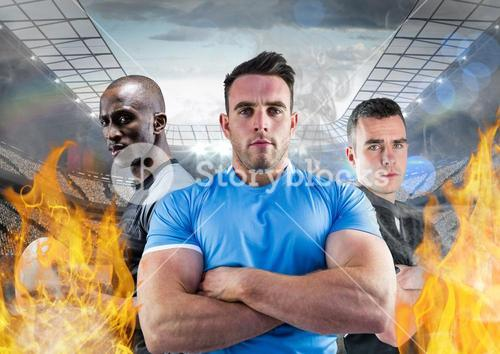 Portrait of american players standing with arms crossed between the fire flame in stadium