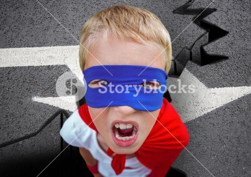 Portrait of aggressive super boy in red cape and blue mask on road