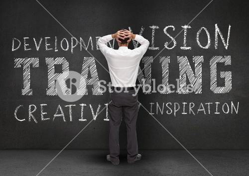 Thoughtful businessman standing against wall with business words