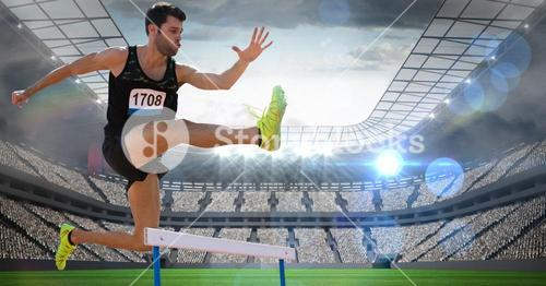 Male athlete jumping above the hurdle in stadium