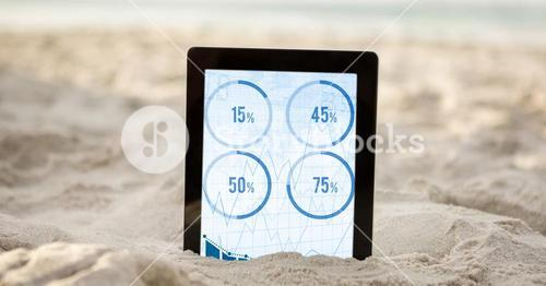 Digital tablet in sand showing four percentage data
