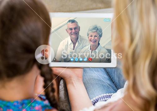 Woman and girl having a video call with senior couple on digital tablet