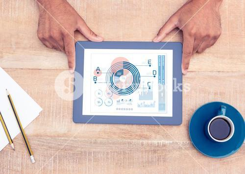 Mans hand holding digital tablet showing graph and chart on wooden table