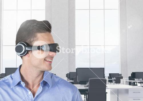 Smiling businessman using virtual reality headset in office
