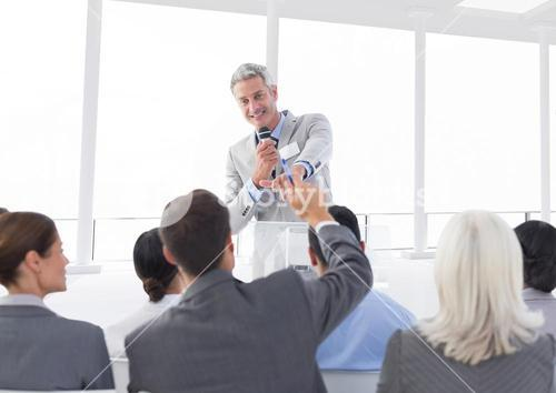 Businessman interacting with colleagues in conference hall
