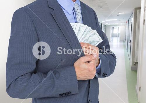 Businessman holding fanned out currency in corridor