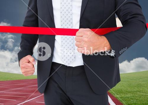 Businessman crossing finish line during race